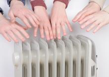 Cold people inside of a home reaching for a heater because it is so cold in Lawton, OK