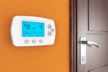 Digital thermostat on orange wall next to wooden door
