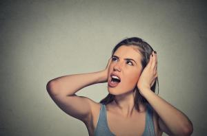 Woman covering her ears to block out noise. Can often be caused by a loud or noisy furnace, which can be fixed by Pippin Brothers Home Services in Lawton Oklahoma
