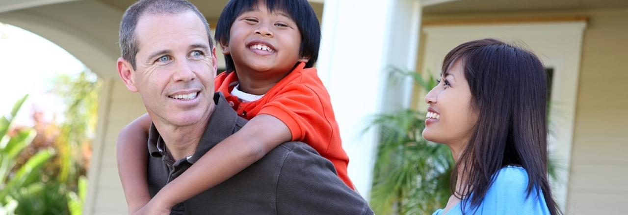 Young boy getting piggyback from father outside of home