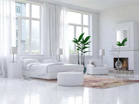 Bedroom with two green plants and an all-white bed, chair, walls, and floors