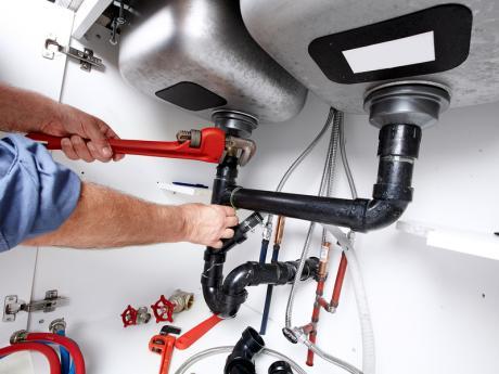 Plumber repairing pipes under sink