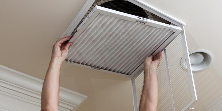 man replacing central air air filter