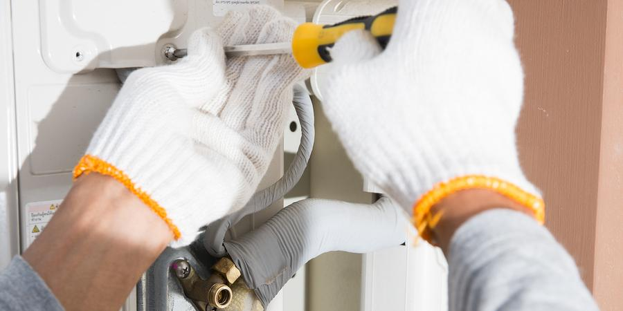 Gloved hands repairing air conditioner with screwdriver