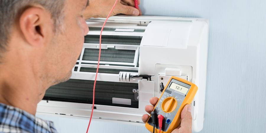 Technician measuring temperature of mini split with HVAC thermometer